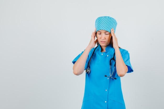 Vrouwelijke arts die aan hoofdpijn in blauw uniform lijdt