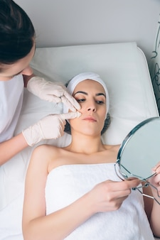 Vrouwelijke arts die aan jonge mooie vrouw de gezichtszones laat zien om kliniekbehandeling toe te passen. geneeskunde, gezondheidszorg en schoonheidsconcept.
