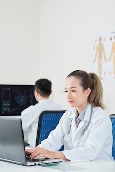 Vrouwelijke arts die aan laptop werkt