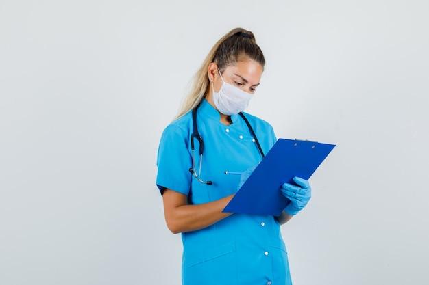 Vrouwelijke arts die aantekeningen op klembord in blauw uniform maakt
