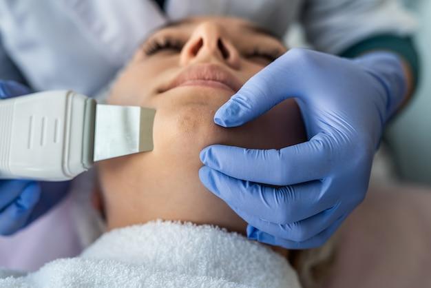Vrouwelijke arts die apparaat voor ultrasone gezichtsbehandeling gebruikt die de procedure van de het gezichtsschil van de cliënt doet. gezondheidszorg