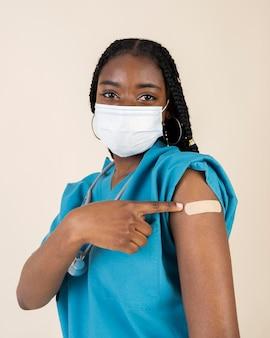 Vrouwelijke arts die arm met sticker toont na het krijgen van een vaccin