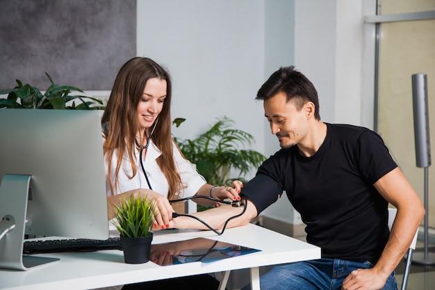 Vrouwelijke arts die arteriële bloeddruk voor patiënt op oude tonometer bij kliniek meet. gezondheidszorg en arts concept
