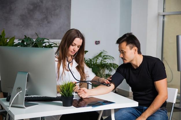 Vrouwelijke arts die arteriële bloeddruk voor patiënt op tonometer bij kliniek meet. gezondheidszorg en arts concept