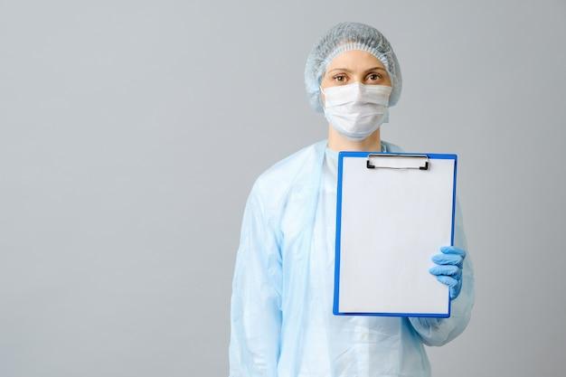 Vrouwelijke arts die beschermend masker draagt dat klembord met witboek toont. geïsoleerd op grijs