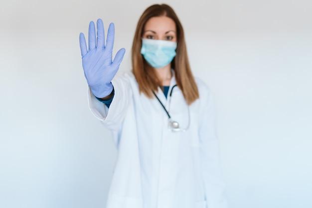 Vrouwelijke arts die beschermend masker en handschoenen draagt