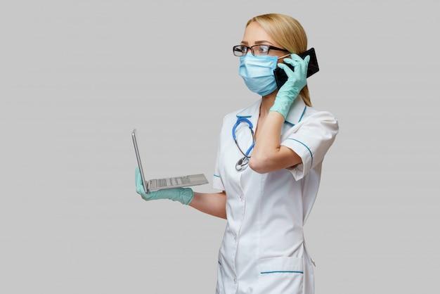 Vrouwelijke arts die beschermend masker en handschoenen en mobiele telefoon draagt