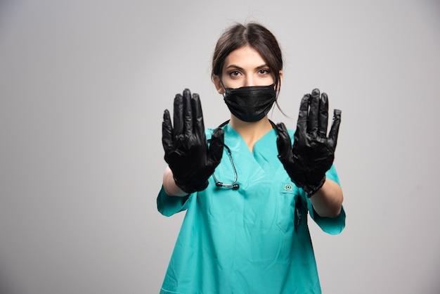 Vrouwelijke arts die beschermend masker en handschoenen op grijs draagt