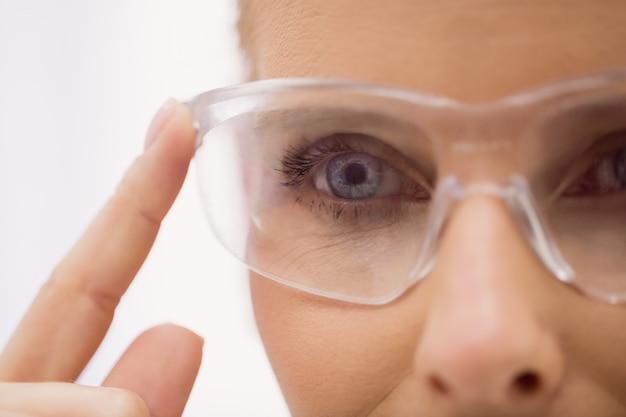 Vrouwelijke arts die beschermende glazen in kliniek draagt