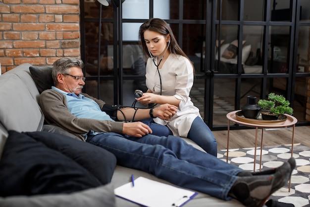 Vrouwelijke arts die bloeddruk meet aan oudere patiënt die op de bank zit.