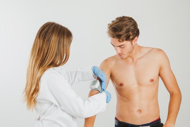 Vrouwelijke arts die bloeddruk meet