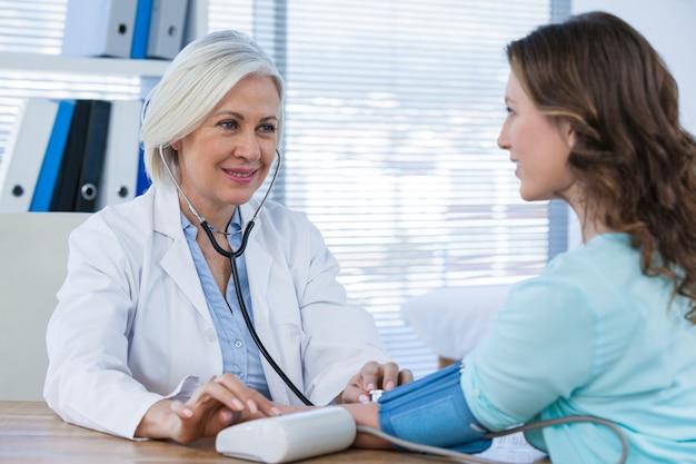 Vrouwelijke arts die bloeddruk van een patiënt controleert