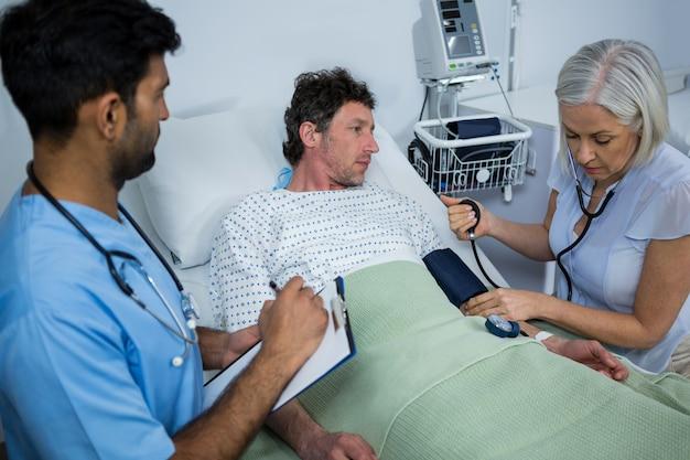 Vrouwelijke arts die bloeddruk van patiënt controleert
