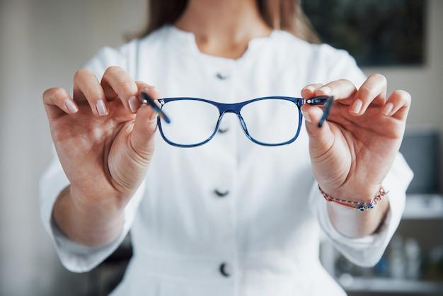 Vrouwelijke arts die de blauwe bril toont door deze in twee handen te houden.