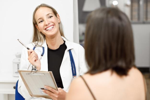 Vrouwelijke arts die de diagnose aan haar jonge vrouwelijke patiënt verklaart.
