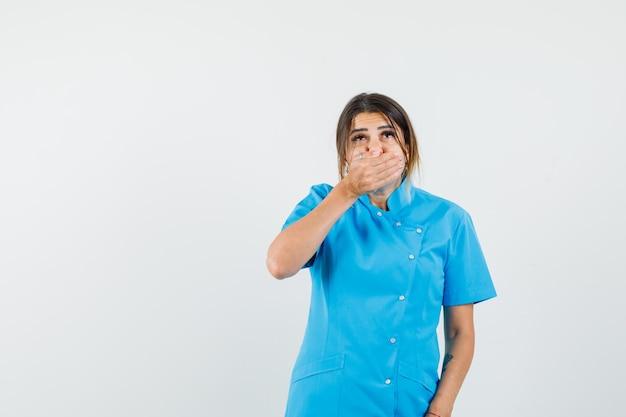 Vrouwelijke arts die de hand op de mond houdt in blauw uniform en er bang uitziet