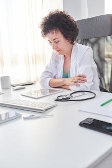 Vrouwelijke arts die de kalender op haar tablet raadpleegt