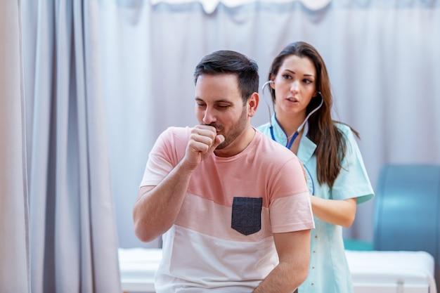 Vrouwelijke arts die de longen van de patiënt met stethoscoop onderzoekt.