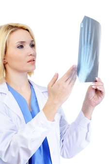 Vrouwelijke arts die de medische x-ray toont - die op wit wordt geïsoleerd
