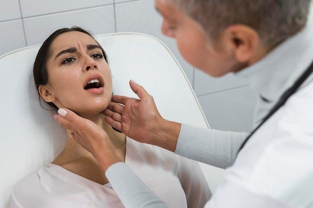Vrouwelijke arts die de mond van een patiënt controleert
