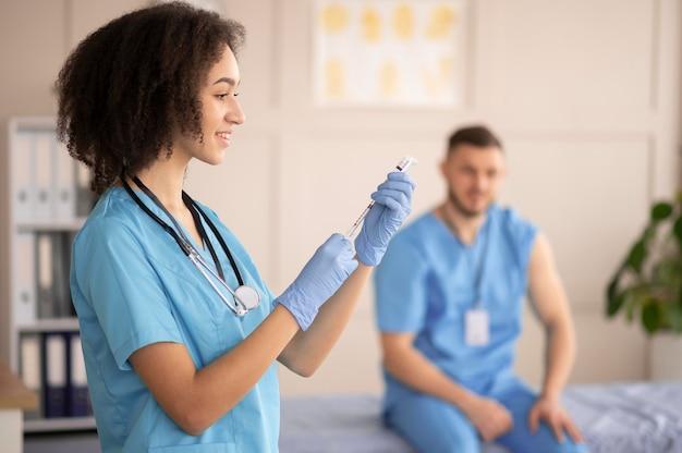 Vrouwelijke arts die de vaccinatie voor haar collega voorbereidt