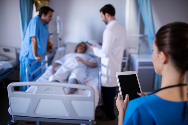 Vrouwelijke arts die digitale tablet in de afdeling gebruiken