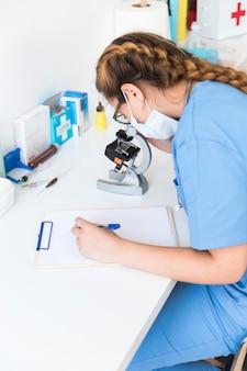 Vrouwelijke arts die door een microscoop kijkt die op klembord in een laboratorium schrijft