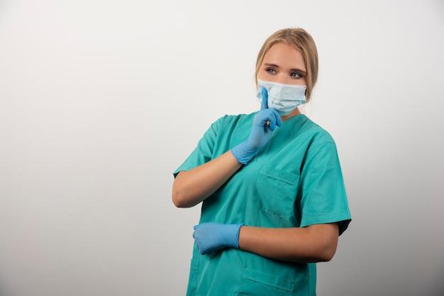 Vrouwelijke arts die duim toont en een medisch masker draagt.
