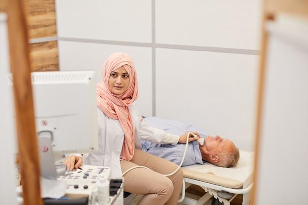 Vrouwelijke arts die echoscopie doet