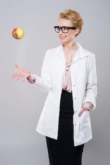 Vrouwelijke arts die een appel werpt