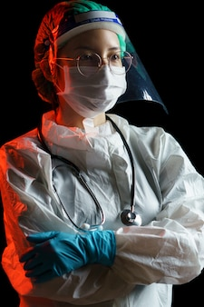 Vrouwelijke arts die een beschermend pak draagt voor coronavirus of covid-19-bescherming. hazmat-pak, gelaatsscherm, handschoenen, masker, stethoscoop.