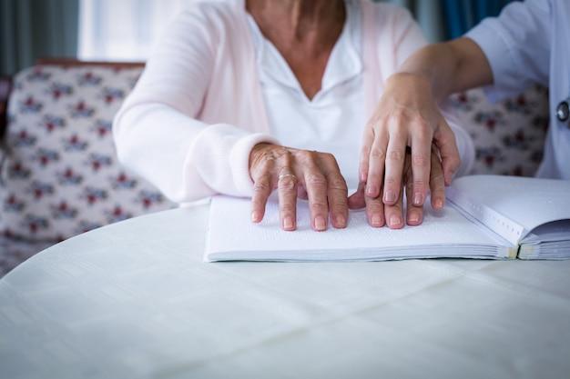 Vrouwelijke arts die een blinde patiënt helpt bij het lezen van het brailleboek