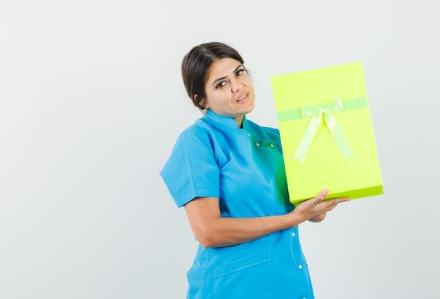 Vrouwelijke arts die een geschenkdoos in een blauw uniform vasthoudt en er zelfverzekerd uitziet