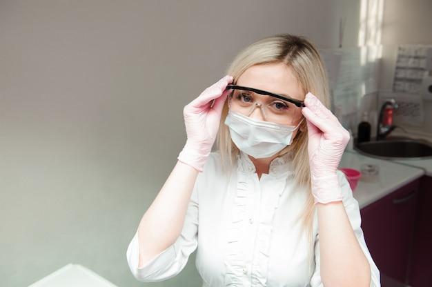 Vrouwelijke arts die een gezichtsmasker en beschermende brillen draagt
