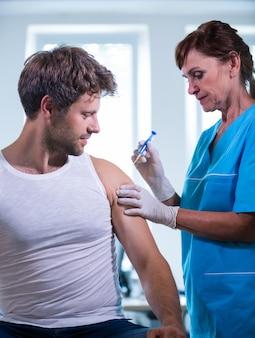 Vrouwelijke arts die een injectie geeft aan een patiënt