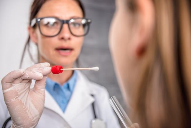 Vrouwelijke arts die een keelcultuur neemt