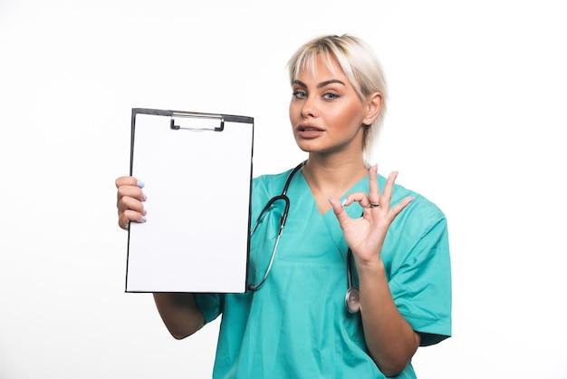 Vrouwelijke arts die een klembord houdt die ok gebaar op wit oppervlak maakt