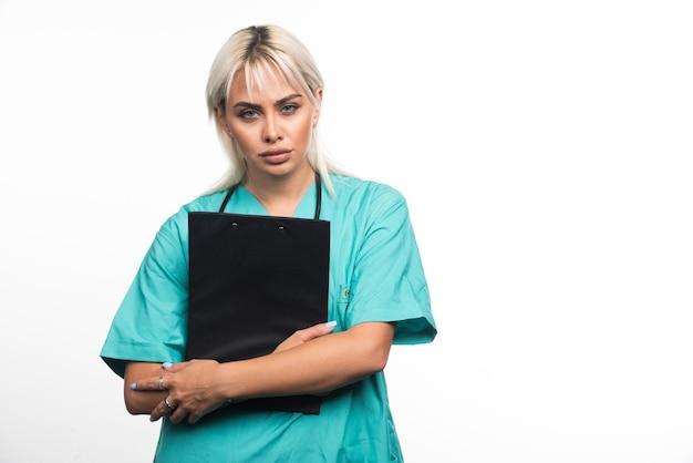 Vrouwelijke arts die een klembord op witte achtergrond houdt die ernstig kijkt. hoge kwaliteit foto