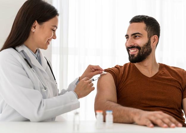 Vrouwelijke arts die een knappe man vaccineert