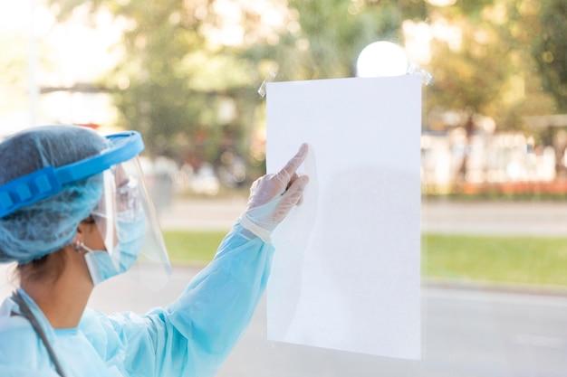 Vrouwelijke arts die een leeg vel papier bekijkt