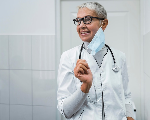 Vrouwelijke arts die een medisch masker met exemplaarruimte opzet