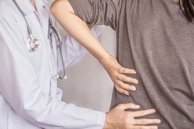 Vrouwelijke arts die een patiënt onderzoekt die aan rugpijn lijdt