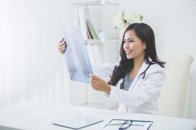 Vrouwelijke arts die een röntgenstraal bekijkt