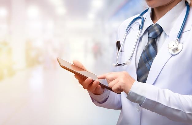 Vrouwelijke arts die een slim apparaat vasthoudt