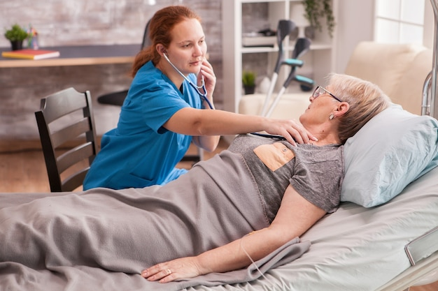 Vrouwelijke arts die een stethoscoop gebruikt om het hart van de oude vrouw in het verpleeghuis te controleren.