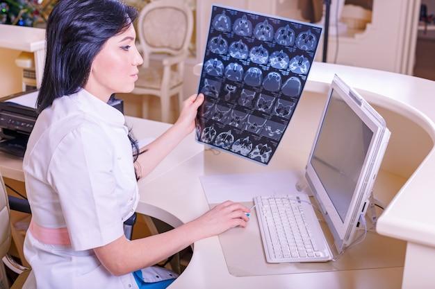 Vrouwelijke arts die een tomografieröntgenstraal bekijkt