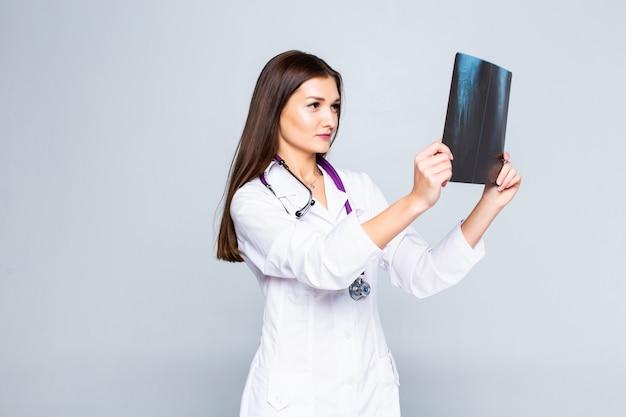 Vrouwelijke arts die een x-ray beeld onderzoekt dat op witte muur wordt geïsoleerd.