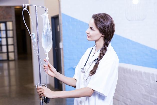 Vrouwelijke arts die een zoute druppel in het ziekenhuis controleert