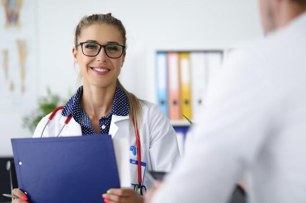 Vrouwelijke arts die en klembord in haar handen glimlacht houdt