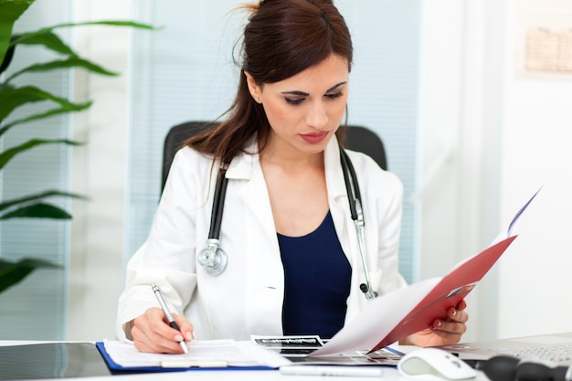 Vrouwelijke arts die geduldig dossier op klembord in bureau leest